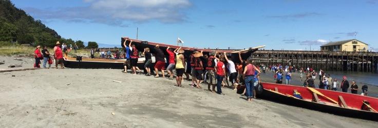 Tribal crew carries canoe onto the beach with local folks lending a hand.